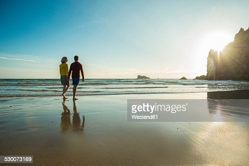 France, Brittany, Camaret-sur-Mer, teenage couple on the beach walking on the beach