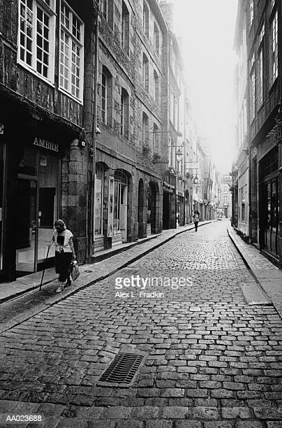 France, Brittany, Dinan, mature woman walking on street (B&W)