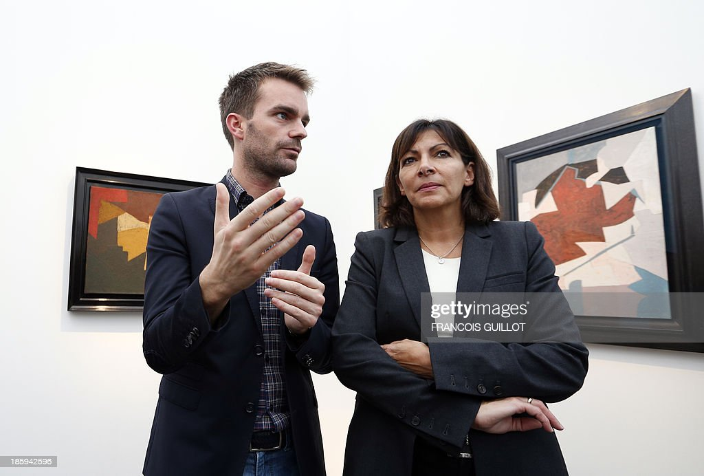CAPTION France' candidate for the 2014 mayoral elections in Paris and Paris socialist deputy mayor Anne Hidalgo (R) and Bruno Julliard, spokesman of the candidate, speak in front of works of Russian artist Serge Poliakoff (1900-1969), on October 26, 2013 during a visit at the FIAC, the International Contemporary Art Fair at Le Grand Palais in Paris. The event runs from October 24 to October 27, 2013. AFP PHOTO/FRANCOIS GUILLOT