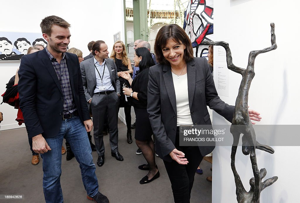 CAPTION France' candidate for the 2014 mayoral elections in Paris and Paris socialist deputy mayor Anne Hidalgo (R), flanked by Bruno Julliard, his spokesman, looks at a sculpture representing rabbits by US Barry Flanagan, on October 26, 2013 during a visit at the FIAC, the International Contemporary Art Fair at Le Grand Palais in Paris. The event runs from October 24 to October 27, 2013.
