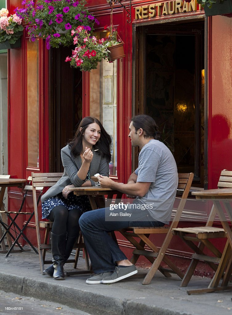 France, Couple sitting in sidewalk cafe