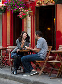 France, Couple sitting in sidewalk cafe