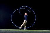France, Dordogne, golfer swinging club on golf course at night, blurred motion