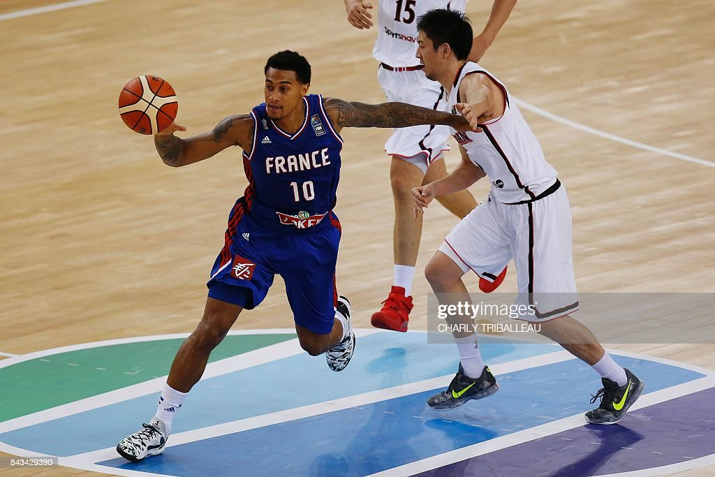 France Edwin Jackson (L) vies with Japan's Makoto Hiejima (R) during the friendly basketball match between France and Japan at the Kindarena hall in Rouen on June 28, 2016. / AFP / CHARLY