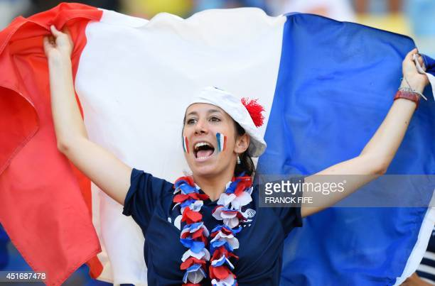 A France fan waves her national flag as she cheers prior to the quarterfinal football match between France and Germany at the Maracana Stadium in Rio...