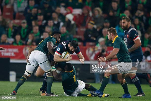 France flanker Loann Goujon is tackled by South Africa loose head prop Tendai Mtawarira during the third rugby union Test match between South Africa...
