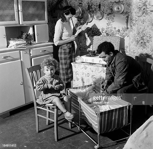 France in July 1956 a family of Nancy in the kitchen mother reading the newspaper the father gives the baby a bottle has in a cradle In its ratings a...