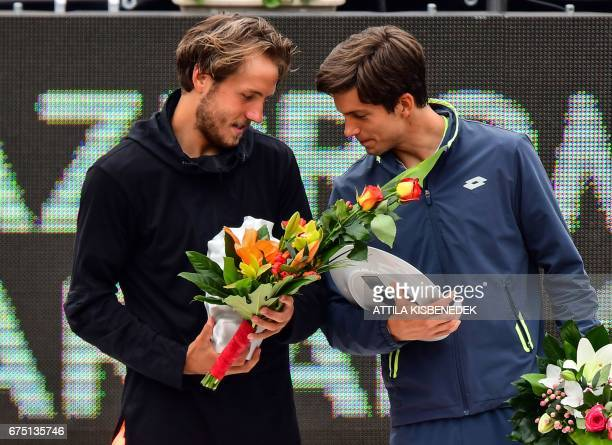 France' Lucas Pouille chats with his opponent Great Britain's Aljaz Bedene on the podium after their final tennis match at the Hungarian Open in...