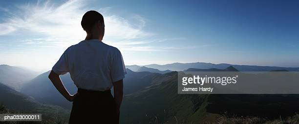 France, man looking out over mountains at sunrise, rear view, panorama