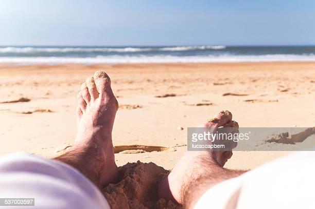 France, Man's legs against sea and sandy beach