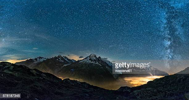 France, Mont Blanc, Lake Cheserys, Milky way and Mount Blanc by night with the valley lighted by the lights of the town of Chamonix