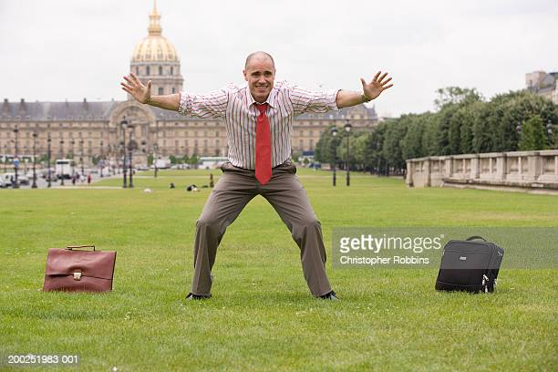 France, Paris, businessman in park playing in goal between briefcases