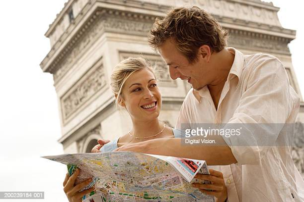 France, Paris, couple checking map, smiling, close-up