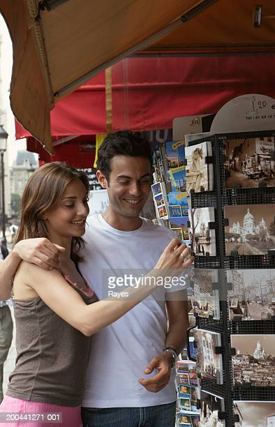 France, Paris, couple looking at rack of postcards, smiling