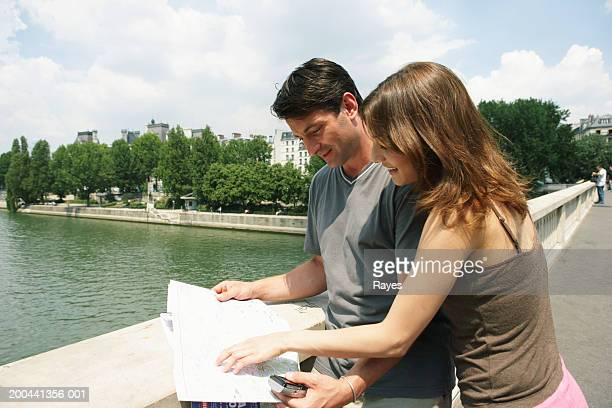 France, Paris, couple on bridge reading map, woman pointing at map
