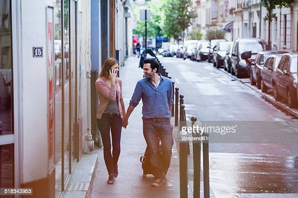 France, Paris, couple on the move with rolling suitcase