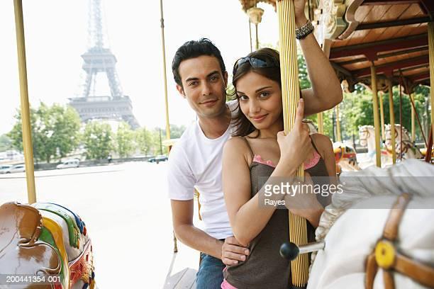 France, Paris, couple riding carousel, man behind woman, portrait