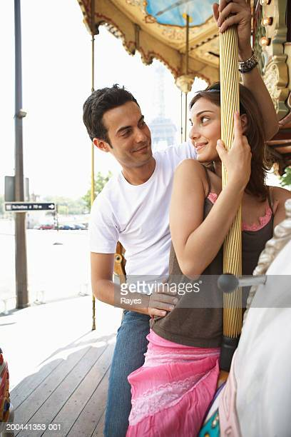 France, Paris, couple riding carousel, man sitting behind woman