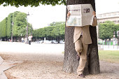 France, Paris, man leaning on tree holding newspaper, obscuring face