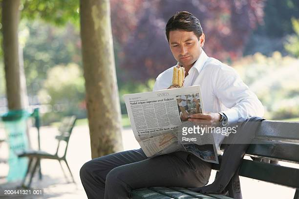 France, Paris, man sitting on bench reading newspaper, eating baguette