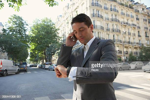 France, Paris, man using mobile phone in street, checking watch