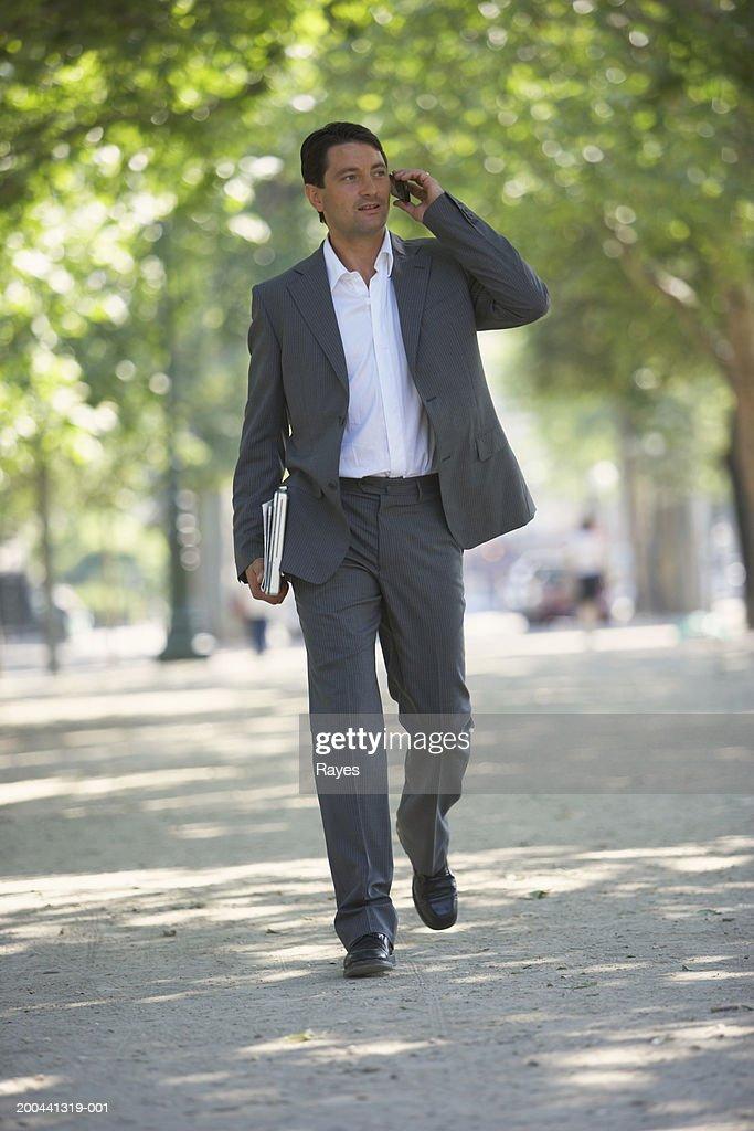 France, Paris, man walking in street using mobile phone