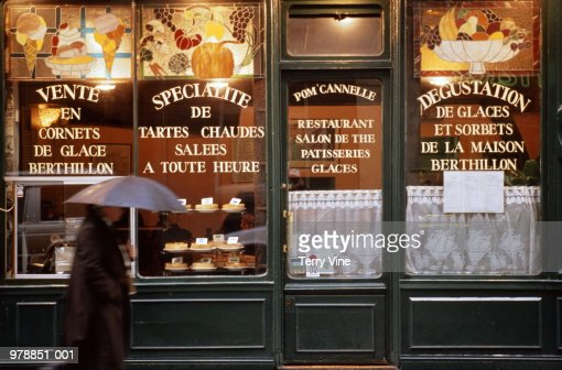 France, Paris, man walking past storefront of pastry shop/tea room : Stock Photo