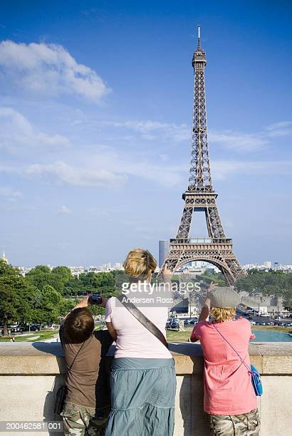 France, Paris, mother and two sons (7-10) photographing Eiffel Tower