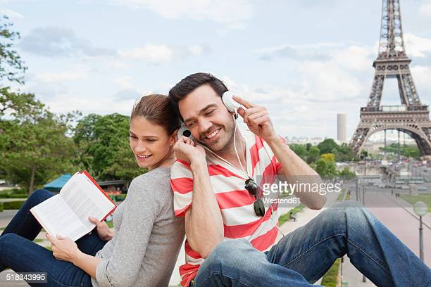 France, Paris, portrait of couple with travel guide and headphones in front of Eiffel Tower
