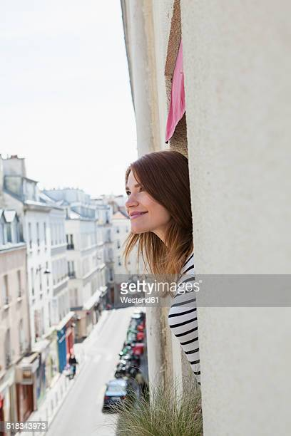 France, Paris, portrait of smiling young woman looking out of hotel window