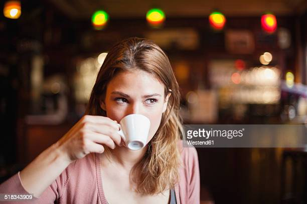 France, Paris, portrait of young woman drinking cup of coffee in a cafe