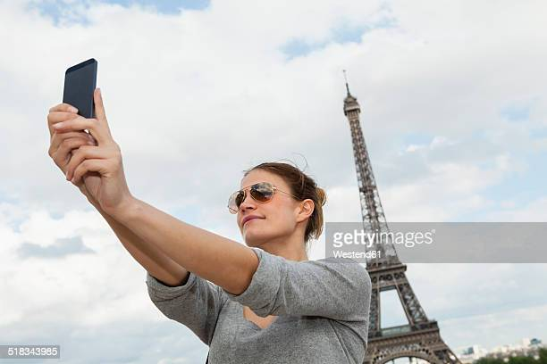 France, Paris, portrait of young woman photographing herself with tablet computer in front of Eiffel Tower