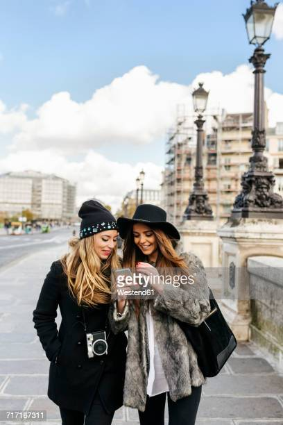 France, Paris, two female tourists walking in the city looking at cell phone