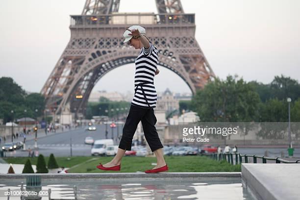 France, Paris, woman balancing on wall near Eiffel Tower