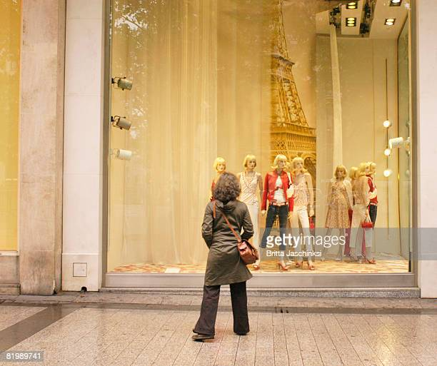 France, Paris, woman looking at window display