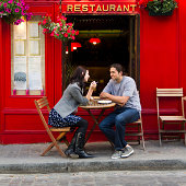 France, Paris, Young couple sitting in sidewalk cafe