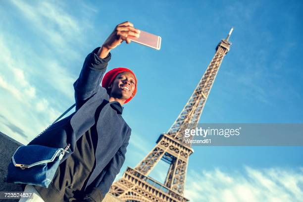 France, Paris, young woman taking selfie in front of Eiffel Tower
