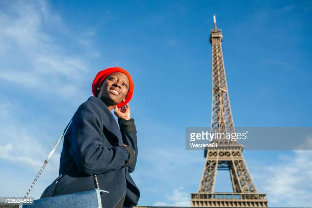 France, Paris, young woman wearing red beret in front of Eiffel Tower