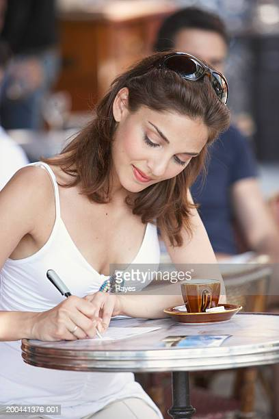 France, Paris, young woman writing postcard in cafe