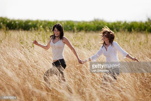 France, Picardie, Albert, Young women running through cornfield