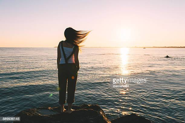 France, Pornichet, woman with blowing hair standing at seafront watching sunset