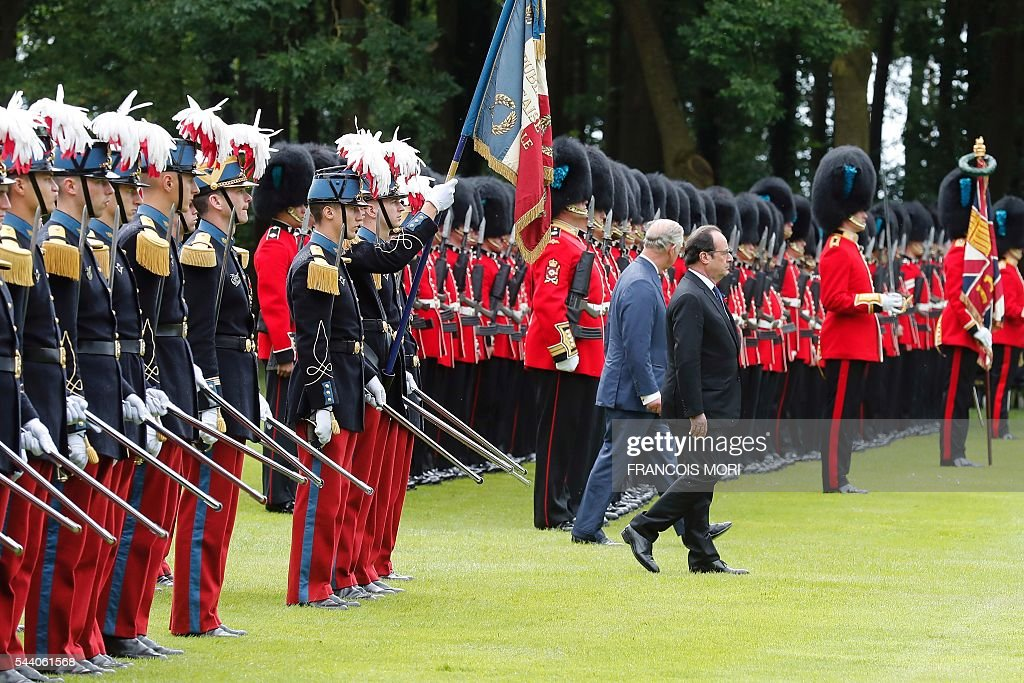 France President Francois Hollande (front) and Britain's Prince Charles (back) walk side by side as they attend the memorial ceremony on July 1, 2016, at the Thiepval Memorial in Thiepval, during which Britain and France will mark the 100 years since soldiers emerged from their trenches to begin one of the bloodiest battles of World War I (WWI) at the River Somme. Under grey skies, unlike the clear sunny day that saw the biggest slaughter in British military history a century ago, the commemoration kicked off at the deep Lochnagar crater, created by the blast of mines placed under German positions two minutes before the attack began at 7:30 am on July 1, 1916. / AFP / POOL / Francois Mori
