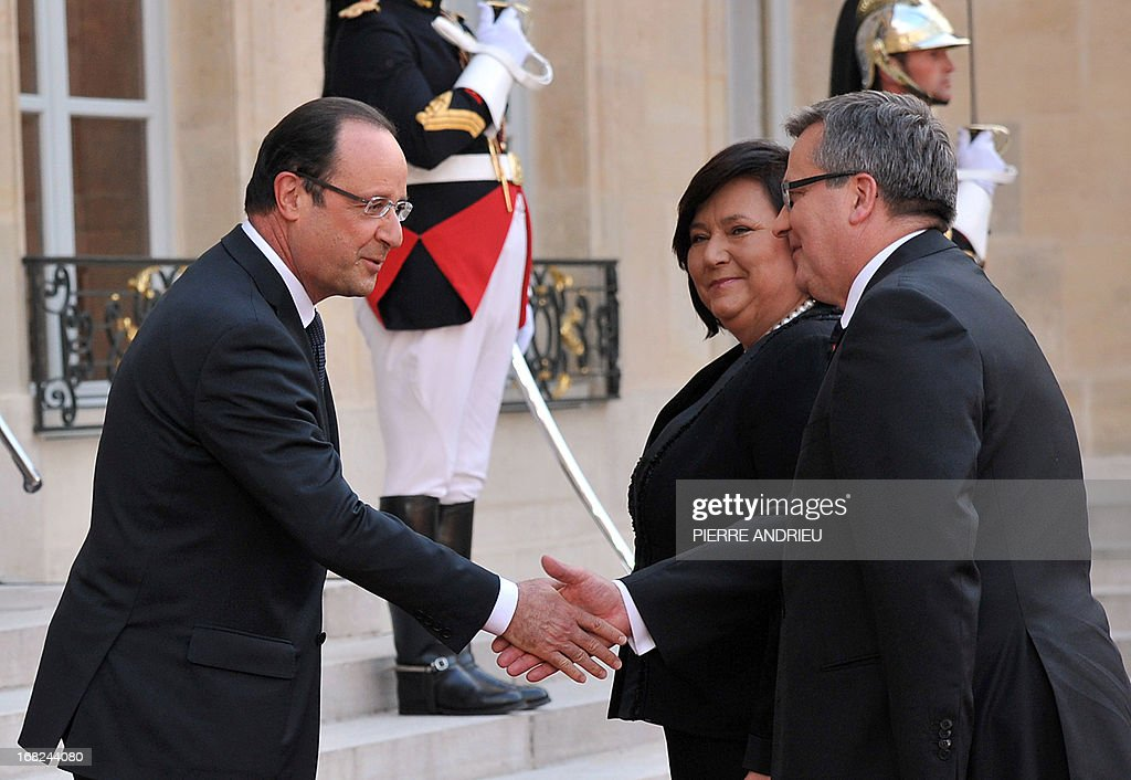 France President Francois Hollande (L) welcomes Poland's President Bronislaw Komorowski (R) and his wife Anna Komorowska (C) upon their arrival at the Elysee presidential palace prior to a State dinner, on May 7, 2013 in Paris. Komorowski is on a two-day State visit in France and will attend the commemorations of the 68th anniversary of the May 8, 1945 victory.