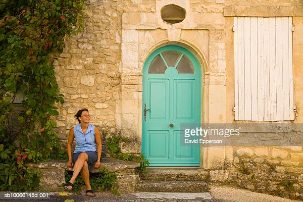France, Provence, Le Beaucet, woman sitting by front door
