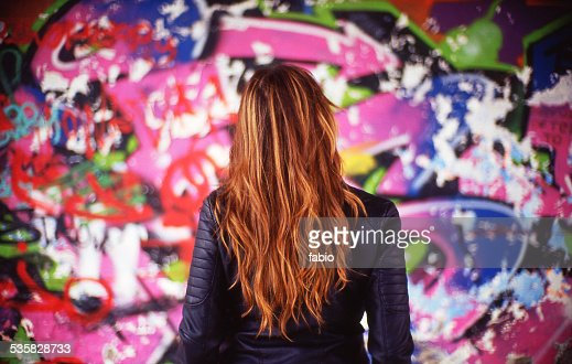France, Rear view of young woman in front of colorful mural