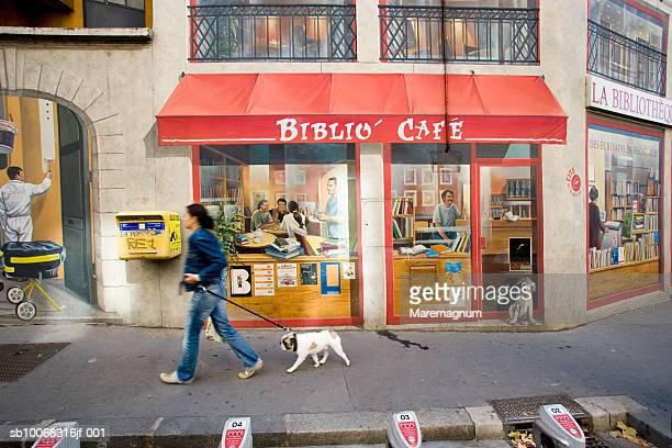 France, Rhone-Alpes, Lyon, Woman with dog passing Lyon Bibliotheque de la Cite mural, blurred motion
