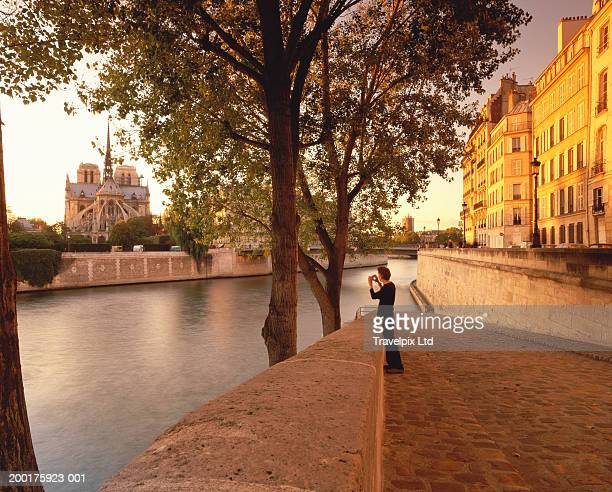 France, River Seine, man photographing Notre Dam Cathedral from bank