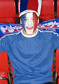 France soccer fan in stand, face painted as Tricolour, portrait