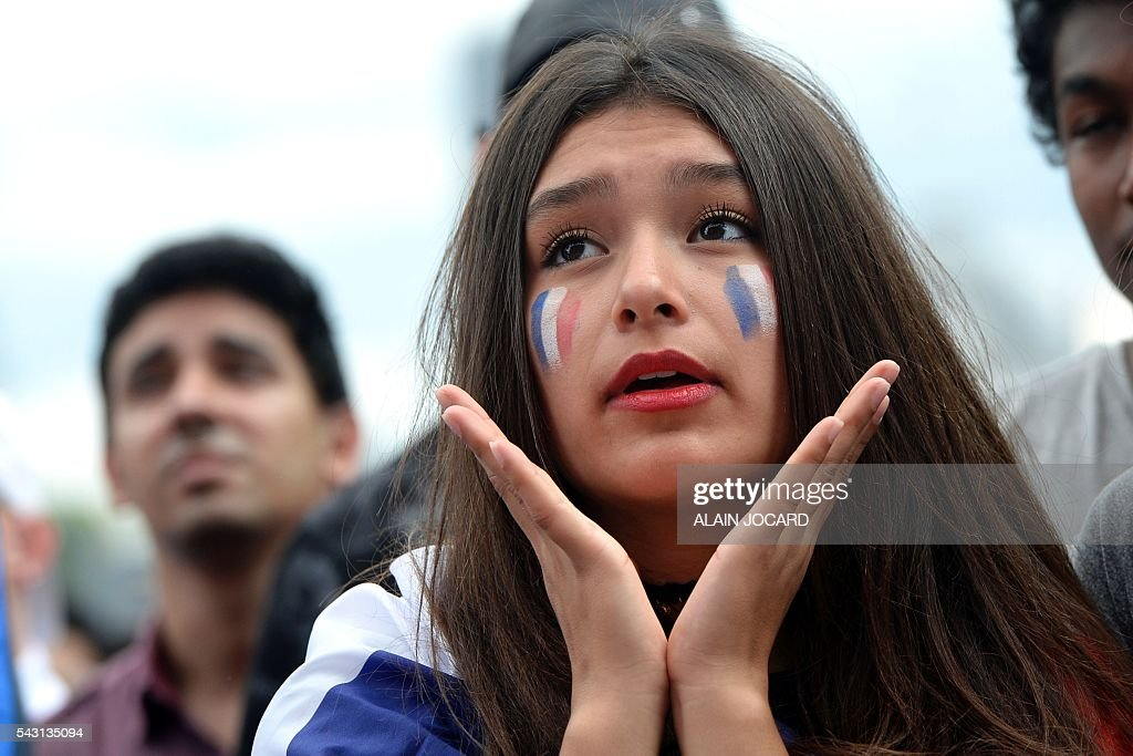 A France supporter reacts as she watches the Euro 2016 tournament round of 16 football match between France and Republic of Ireland on June 26, 2016 at the Champ-de-Mars fanzone in Paris. / AFP / ALAIN