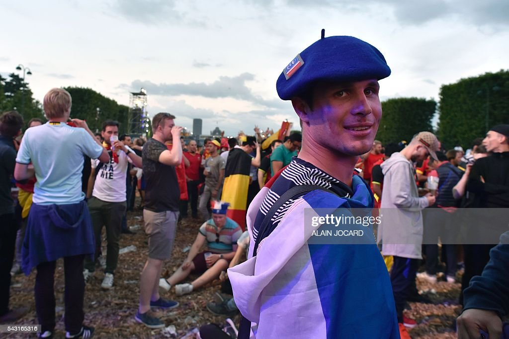 A France supporter watches the Euro 2016 tournament round of 16 football match between Hungary and Belgium at the Champs-de-Mars fan zone in Paris on June 26, 2016. / AFP / ALAIN